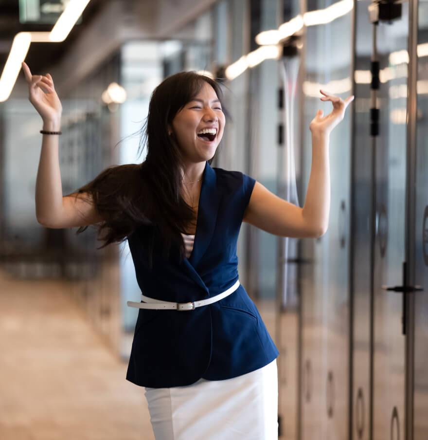 Junge Frau in blauer Bluse steht auf dem Flur und freut sich