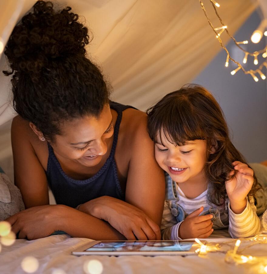 Frau liegt mit Kind in Hoehle aus Decken und schaut sich etwas auf dem Tablet an