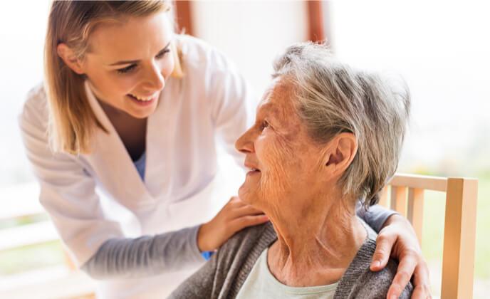 Altenpflegerin spricht mit Bewohnerin