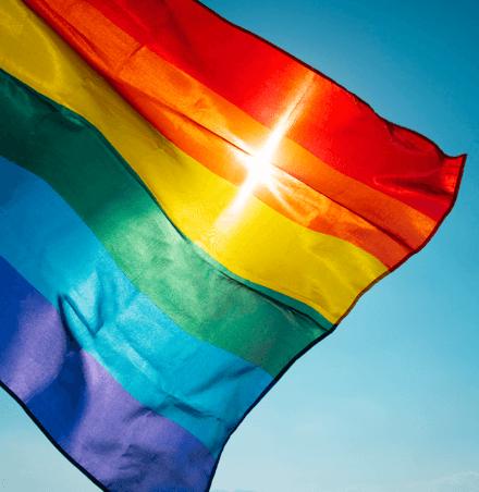 Regenbogenflagge vor blauem Himmel mit Sonnenschein