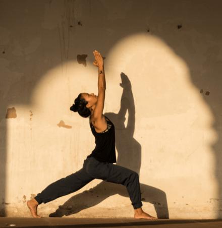 Frau in dunkler Kleidung vor heller Wand in Yoga Position