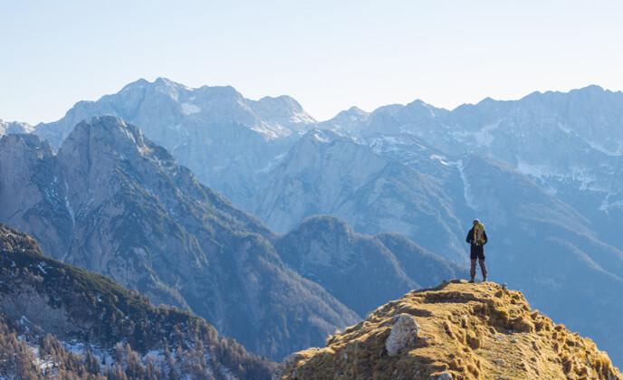 bergsteiger steht auf bergkuppe und schaut auf bergkette