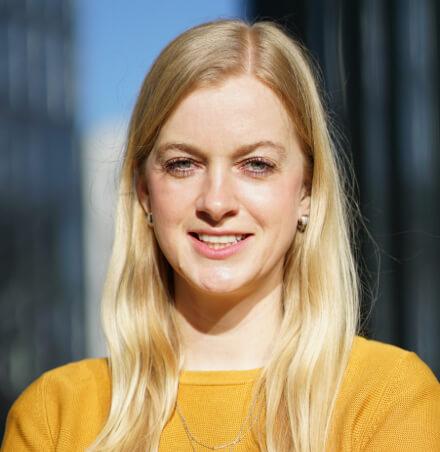 Junge Frau mit blonden Haaren und gelben Oberteil