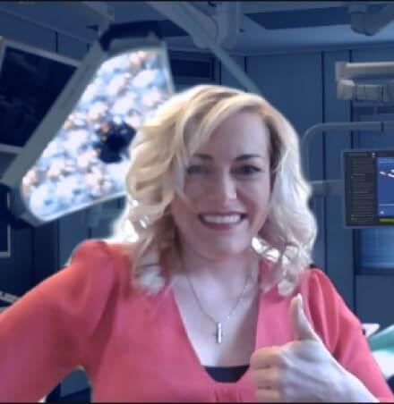 Frau mit blonden gewellten Haar und rosa Pullover steht in einem Behandlungszimmer
