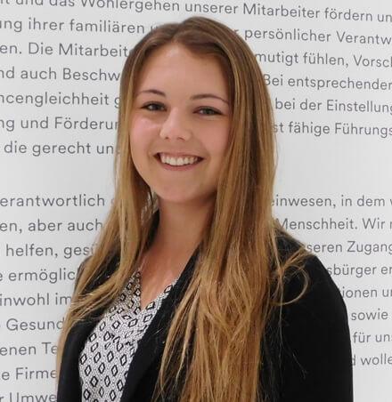 Junge Frau mit blonden langen Haar und bedruckter Bluse steht vor Wand mit Text