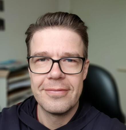 Mann mit brauen zurueckgekaemmten Haar und dunkler Brille sitzt auf schwarzem Schreibtischstuhl
