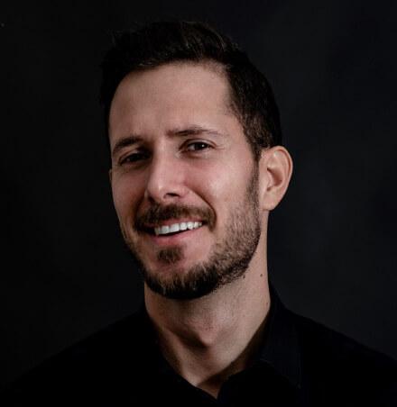 Junger Mann mit dunklen Haaren und dunklen Bart steht vor einer dunklen Wand