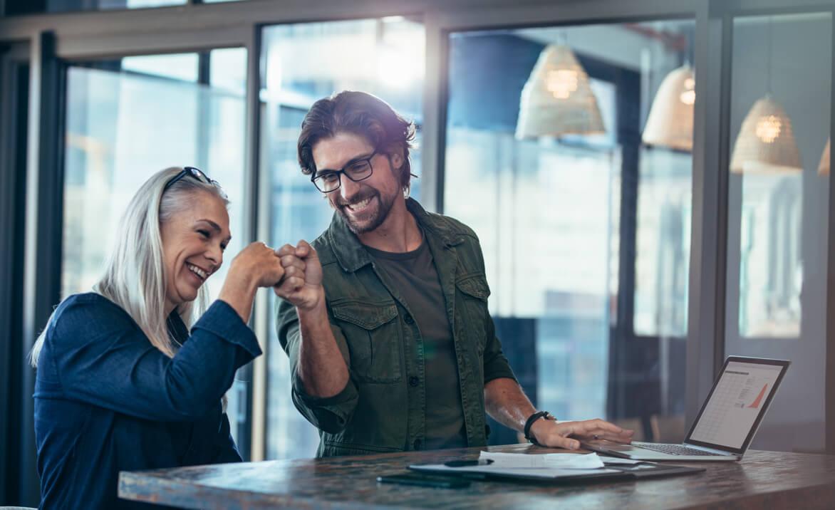 Zwei Kollegen am Stehtisch mit Laptop geben sich einen Handschlag