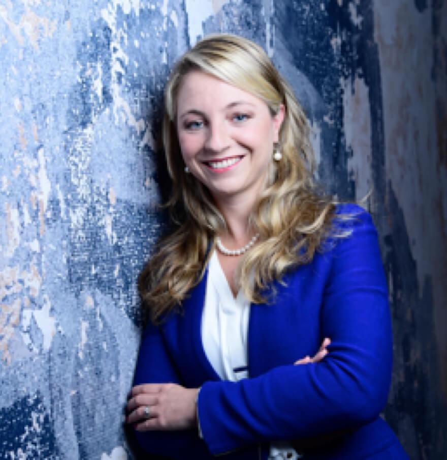 Junge Frau im Business Anzug mit blonden Haar lehnt an einer Wand