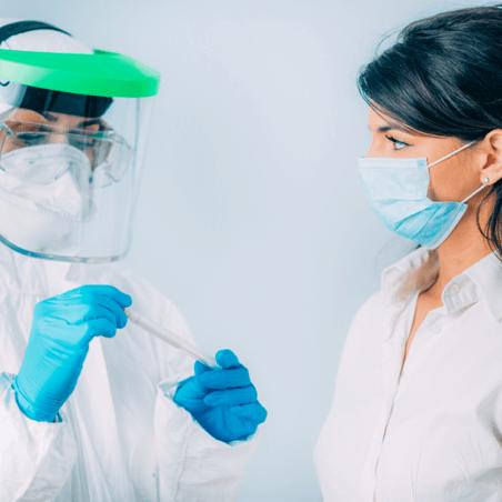 Wissenschaftlerinnen mit Maske betrachten Röhrchen mit Inhalt