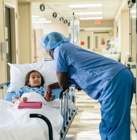 Doctor haelt die Hand eines Kindes, dass im Krankenbett liegt
