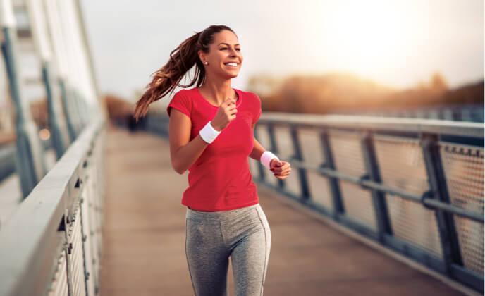 Junge Frau mit rotem T-Shirt joggt ueber eine Bruecke