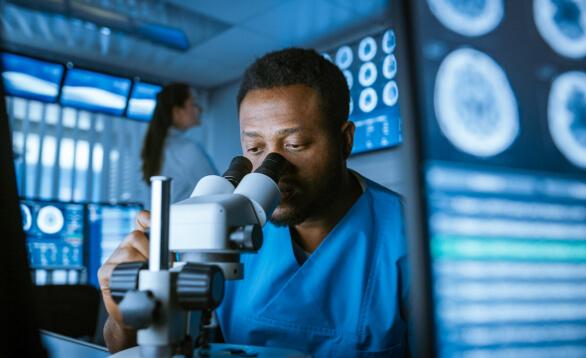 Labormitarbeiter mit blauem Kittel schaut durch Mikroskop