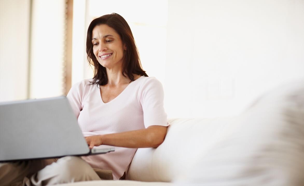 Bruenette Frau mit rosa T-Shirt sitzt an weissen Laptop