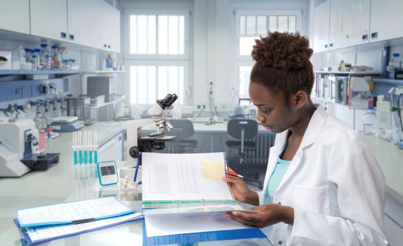 Wissenschaftlerin im Labor liest in Unterlagen