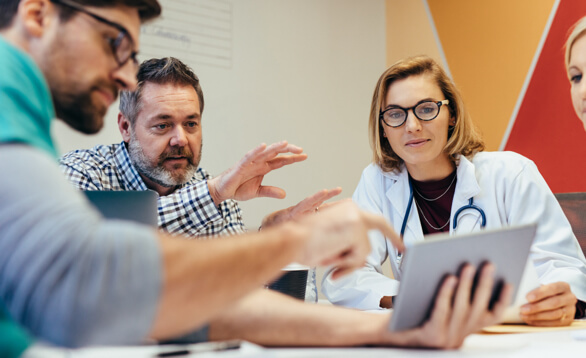 Aerztin mit scharzer Brille und Stetoskop sitzt im Gespraech mit Wissenschaftlern