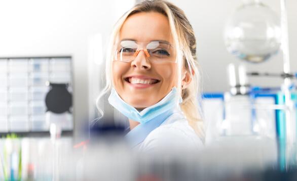 Wissenschaftlerin mit Schutzbrille und medizinischer Mund Nasen Maske
