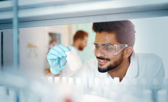 Wissenschaftler hat kleinen weißen Behaelter in der Hand
