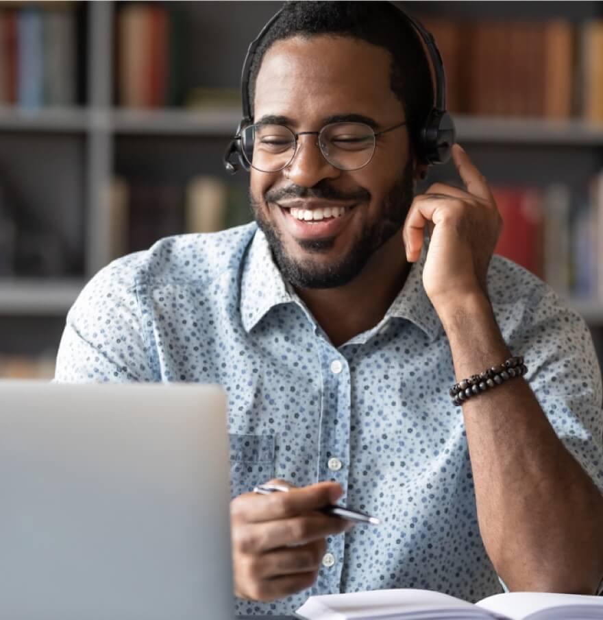 Mann sitzt mit Headset vor einem Laptop am Schreibtisch