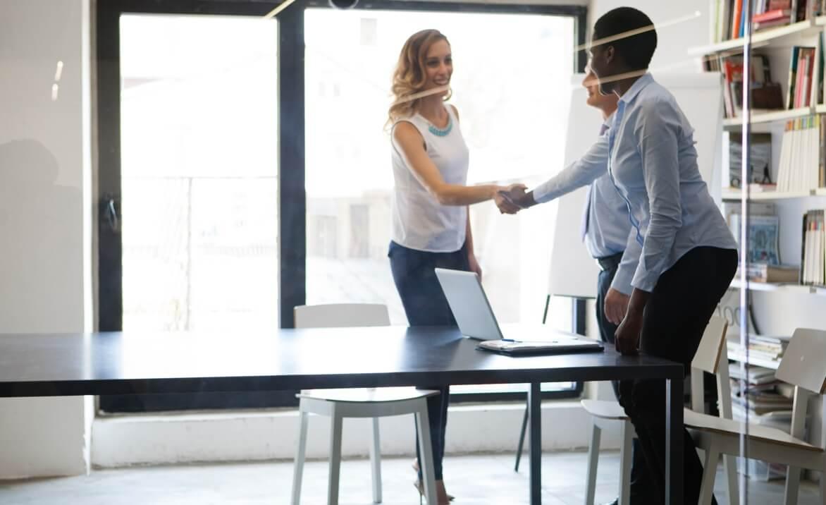 Drei Menschen in einem Meetingraum, zwei reichen sich die Hand