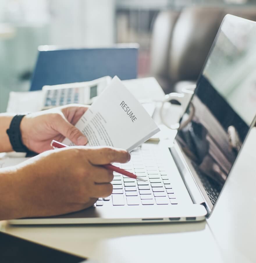 Hand haelt Unterlagen in der Hand mit Laptop im Hintergrund