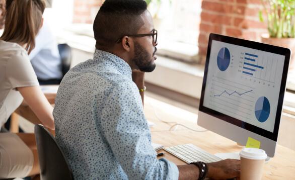 Mitarbeiter sitzt vor einem Bildschirm der Statistiken anzeigt