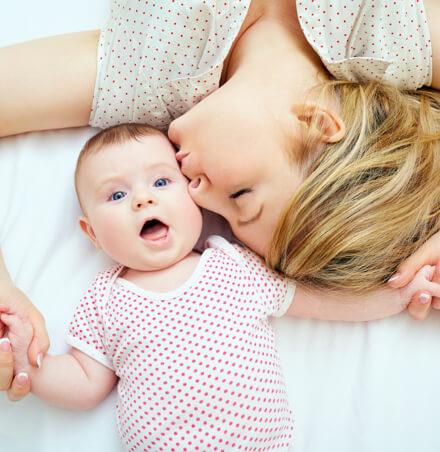 Mutter gibt Baby mit blauen Augen einen Kuss auf die Wange