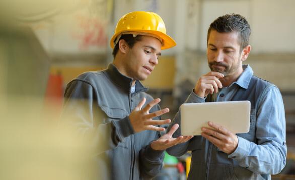 Ingeneure mit gelbem Helm besprechen Aufgaben am Tablet