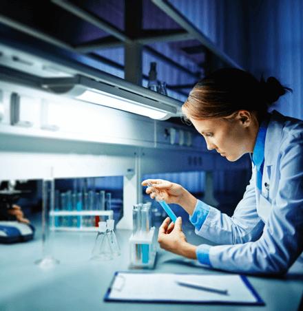 Wissenschaftlerin betrachtet Reagenzglas mit blauem Inhalt