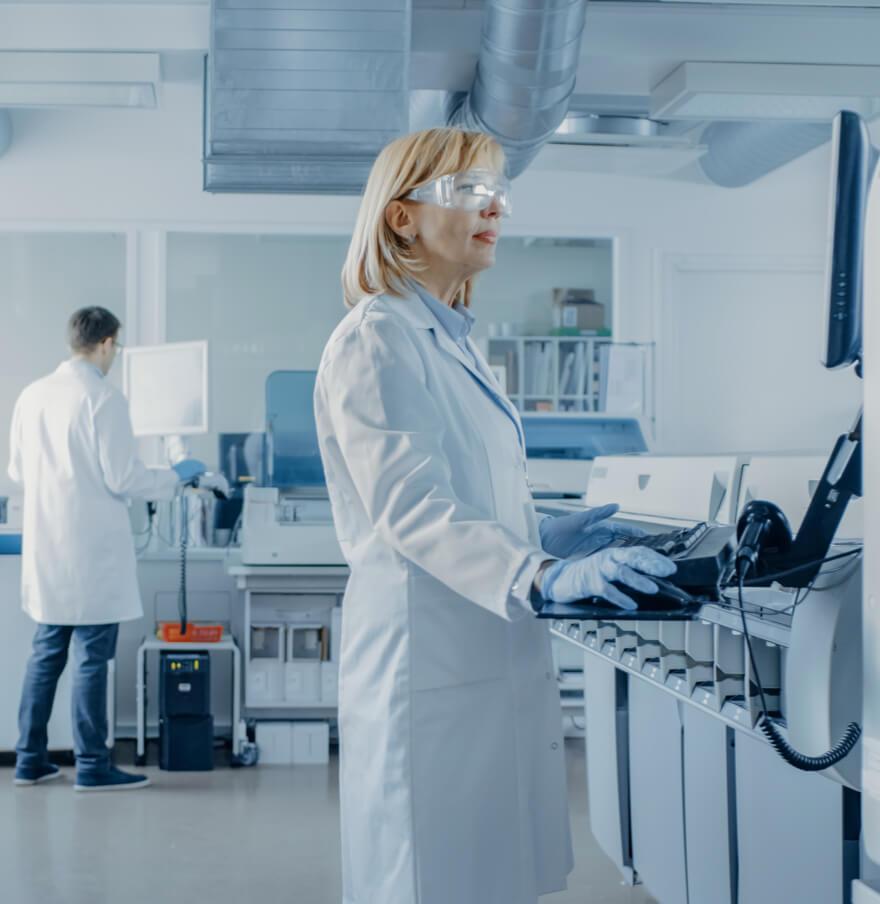 Wissenschaftlerin im Labor steht am Computer