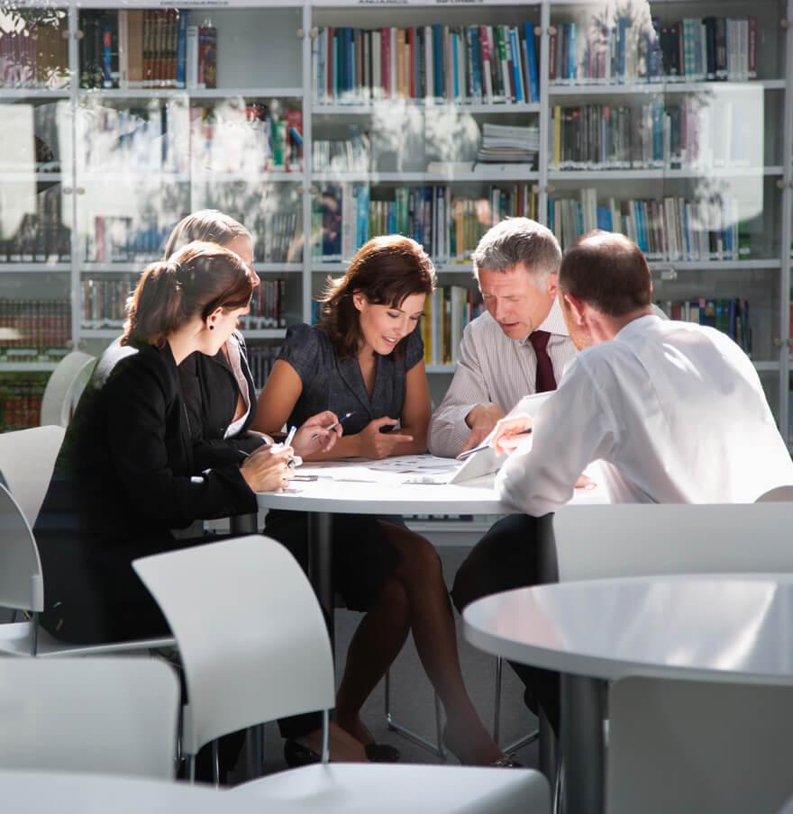Team sitzt am Tisch und redet ueber Unterlagen