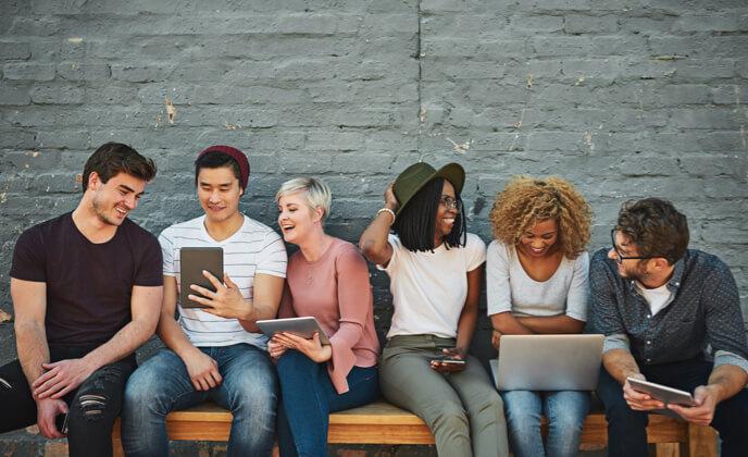 Studenten sitzen auf einer Bank und schauen auf Tablets
