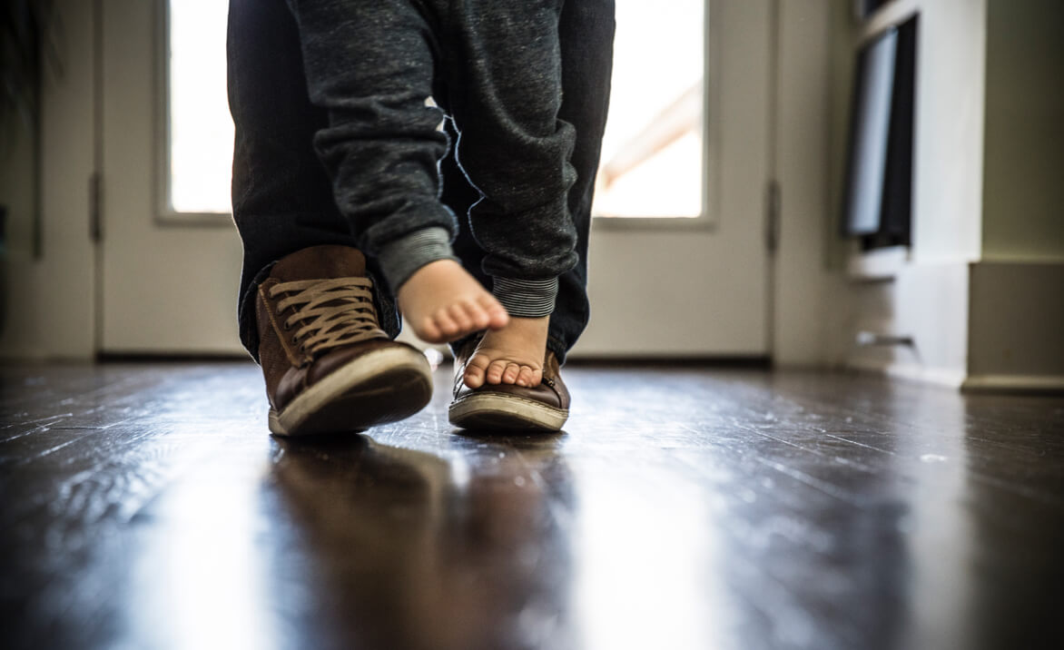 Baby-/Kinderfuesse stehen barfuss auf Schuhen von Vater