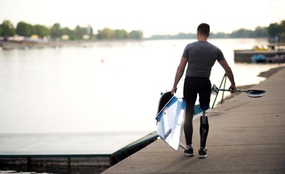 Mann auf einem Steg traegt Kajak und Paddel mit jeweils einer Hand zum Wasser